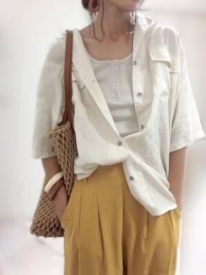 白いトップスに白いシャツをルーズに羽織って黄色のテーパードパンツを履く女性