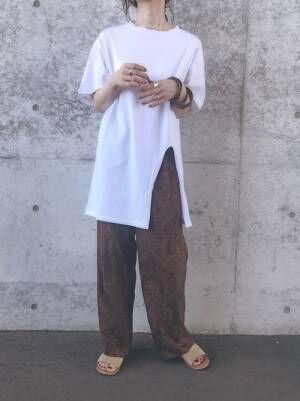 白のスリット入りTシャツにブラウンのペイズリー柄パンツを合わせた女性