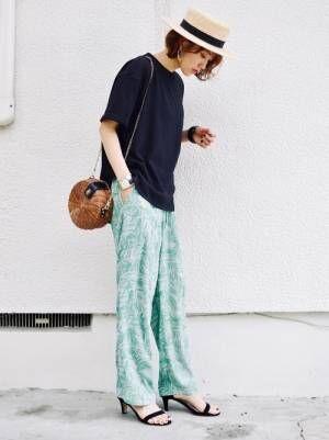 黒のTシャツにグリーンのリーフ柄パンツを合わせた女性