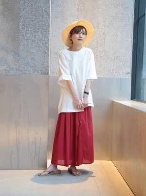 白のビッグTシャツに赤いフレアスカートを合わせた女性