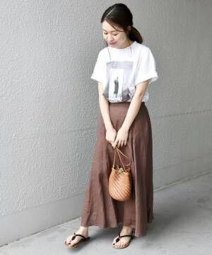 白のフォトTシャツにブラウンのリネンフレアスカートを合わせた女性