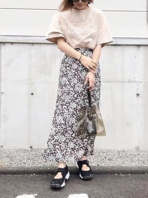 ベージュのTシャツにブラウンの花柄スカートを合わせた女性