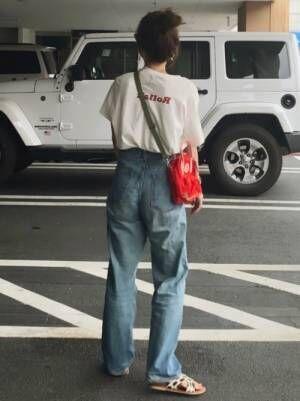 レッドのバッグプリントTシャツを着る女性