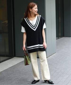 白のロゴTシャツにオフホワイトのリブパンツを合わせて、黒のチルデンベストをレイヤードした女性