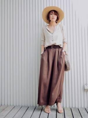 ベージュのヘンリーネックTシャツにブラウンのパンツを合わせた女性
