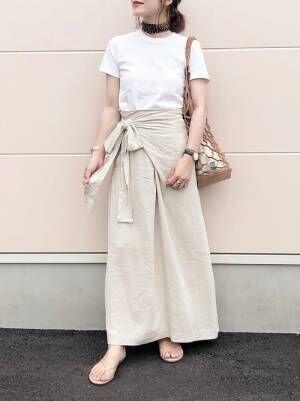 白Tにベージュのラップスカートを合わせた女性