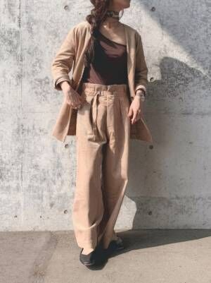 ベージュのジャケットとパンツのセットアップのインナーにブラウンのワンショルダータンクを着た女性