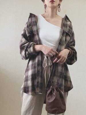 白のワンショルタンクトップにベージュのパンツを合わせて、ブラウン系のチェック柄シャツを羽織った女性