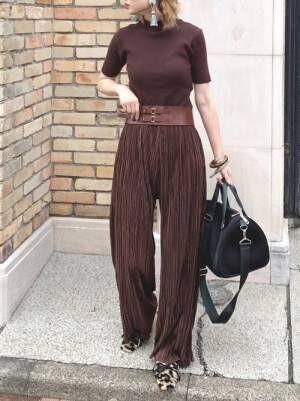 ブラウンの半袖ニットにブラウンのパンツを合わせた女性
