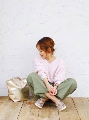 パステルピンクのニットにカーキのベイカーパンツを合わせて、パイソン柄のスリッポンを履いた女性