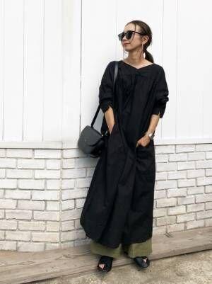 黒のワンピースにカーキのパンツを合わせた女性