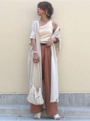 白のワンショルダータンクにブラウンのパンツを合わせて、ベージュのシャツワンピをはだけさせて羽織った女性