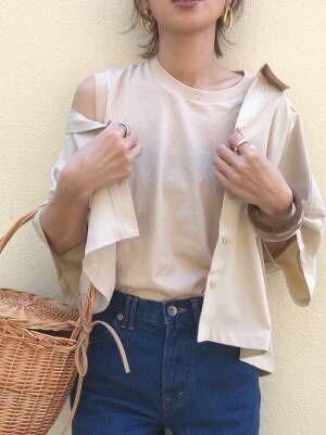 ベージュのタンクトップとデニムにベージュのシャツを抜き襟ではだけさせて羽織った女性