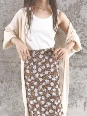 白のタンクトップにブラウンの花柄スカートを合わせて、ベージュのカーディガンをはだけさせて羽織った女性