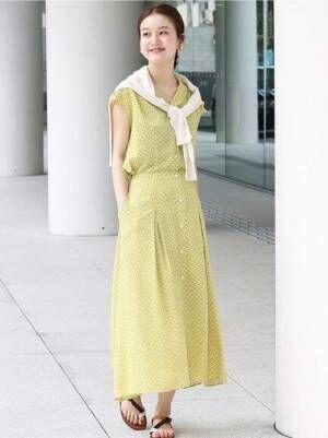 黄緑の柄ワンピに白カーデを肩掛けしている女性