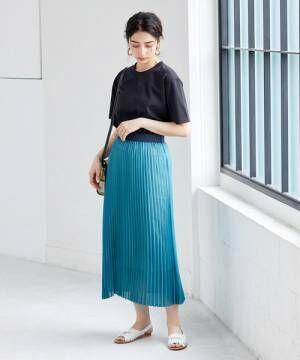 ネイビーのTシャツにブルーのプリーツスカートを合わせた女性