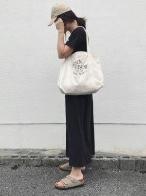 黒のTシャツワンピにベージュのキャップをかぶった女性