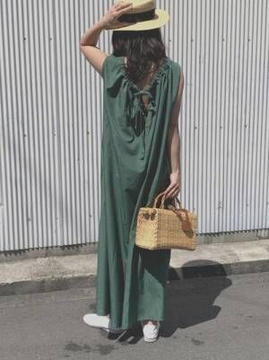 グリーンのワンピースにカンカン帽を合わせた女性