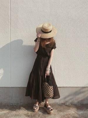 黒のティアードワンピースに麦わら帽子をかぶった女性