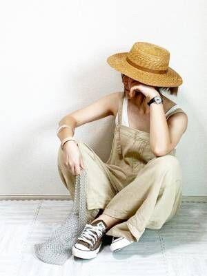 白のタンクトップにベージュのサロペットを合わせてカンカン帽をかぶった女性