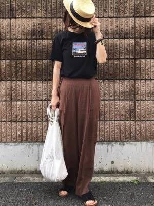 黒のTシャツにブラウンのパンツを合わせて、カンカン帽をかぶった女性
