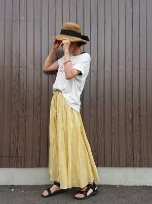 白のロゴTシャツにイエローのスカートを合わせて、麦わら帽子を合わせた女性