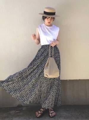 白のノースリトップスに花柄スカートを合わせて、カンカン帽をかぶった女性