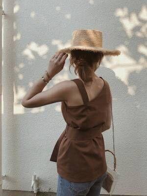 ブラウンのワンショルトップスに麦わら帽子を合わせた女性