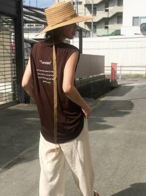 ブラウンのバックプリントタンクトップにオフホワイトのパンツを合わせて麦わら帽子をかぶった女性