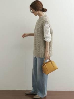 グレーのニットベストを着る女性