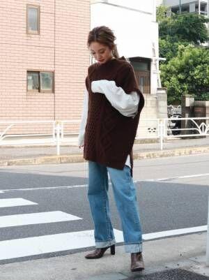 ブラウンのニットベストを着る女性