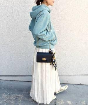 ライトグリーンのフーディ―に白のスカートを合わせた女性