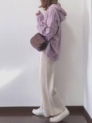 パープルのパーカーにベージュのリブパンツを合わせた女性