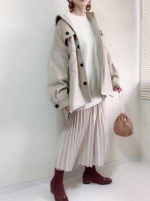 白ニットにベージュコート、ベージュのプリーツスカートと赤っぽいブーツを合わせたコーデ