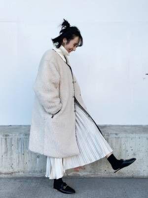 プリーツスカートにボアコートの女性