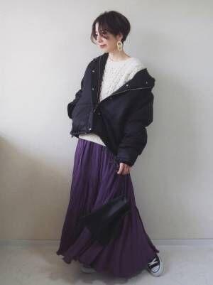 s白のゆるニットに中綿ジャケットを羽織って、パープルのマキシスカートを合わせた女性