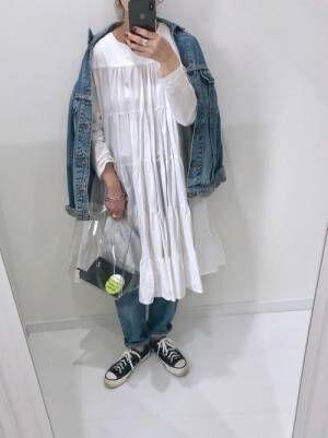 デニムジャケットにコットンシャーリングワンピ白を着てデニムを履く女性