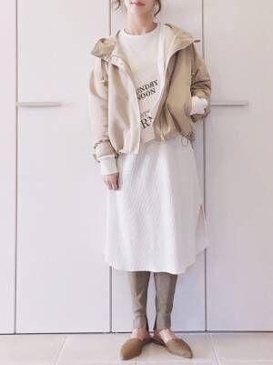 白いワンピースにベージュのマウンテンパーカーを羽織る女性
