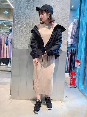 ベージュのニットワンピースに黒いマウンテンパーカーを羽織る女性