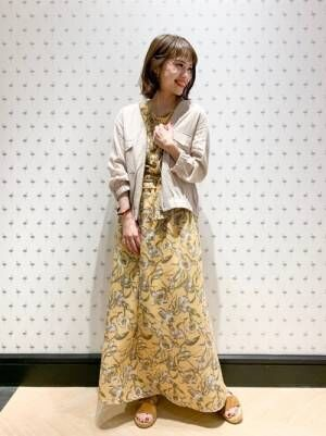 黄色の花柄ワンピにオフホワイトのブルゾンを羽織る女性