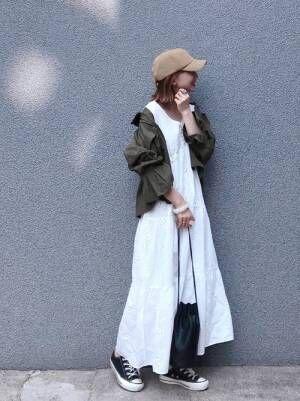 白ワンピースにミリタリージャケットを羽織ってキャップをかぶる女性