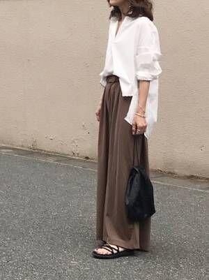 白シャツにブラウンパンツを履く女性